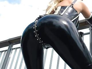 Sexy blonde lady black shiny latex catsuit