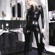 Sexy blonde lady black shiny latex catsuit at home
