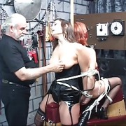 Two leather-corseted bdsm captives get bound and roped together by older dude